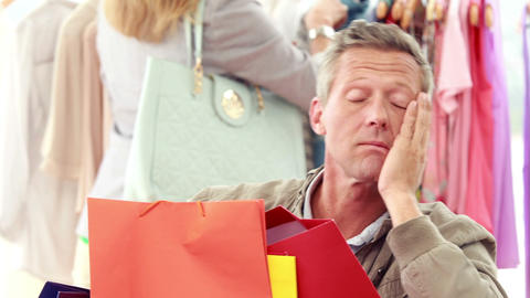 Bored man with shopping bags sitting in front of his girlfriend Footage