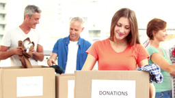 Happy Volunteer Family Separating Donations Stuffs stock footage