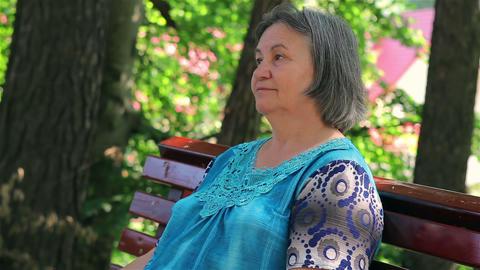 Elderly woman sitting on park bench Footage