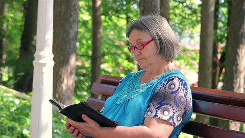 Senior woman reading bible in the park Footage
