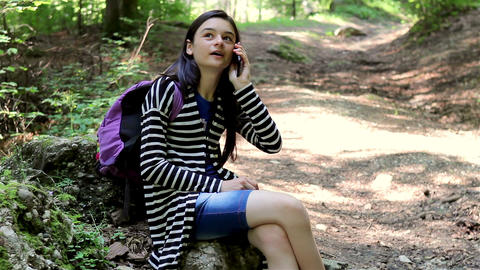 Young girl talking on smartphone in forest Footage