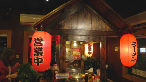 asian woman sits at japanese restaurant with lanterns Footage