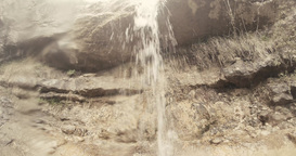 small waterfalls flow of water in the rocks and stones in the mountains Footage