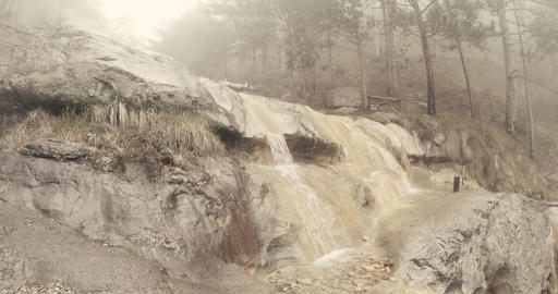 small waterfalls flow of water on the rocks in the fog in a mountain forest Footage