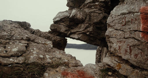 through a window into a mountain cliff is seen as the sea mist Footage
