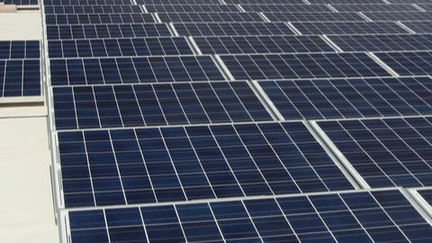 A grid of solar panels on rooftop angled toward sun generates electricity to ele Footage