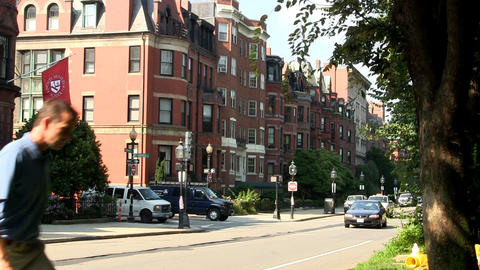 Brownstone buildings on beacon street in Boston on summer day as cars pass by th Footage