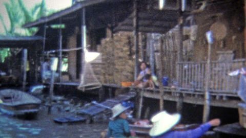 1973: Travel Southeast Asian waterways with merchant boathouses Footage