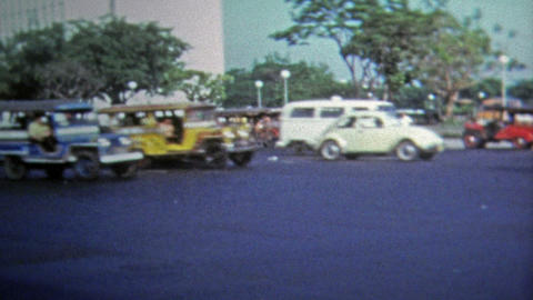 1973: Classic Jeepney driving past busy urban intersection Footage