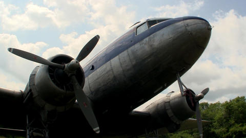 A DC-3 transport aircraft parked on grass at Cape Cod Airfield against blue sky  Footage