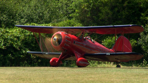 Red biplane waits at one end of airfield runway near trees making last minute ch Footage