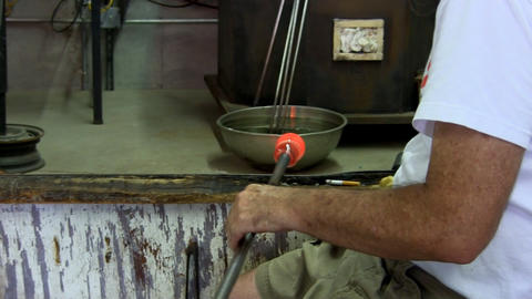 Glass artist rolls gather of glass on punty across bench for shaping Footage
