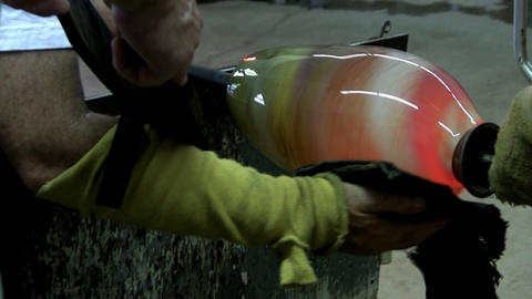 Glass artist uses puffer and Kevlar pad in shaping mouth of spiral colored vase Live Action