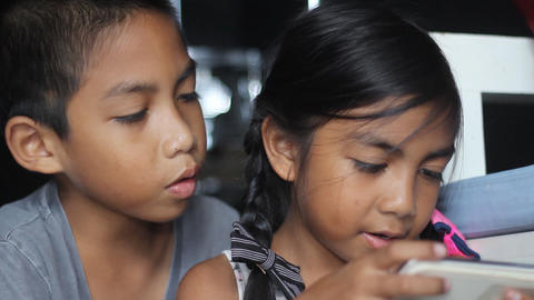 Brother and sister having fun with game in smartphone Footage