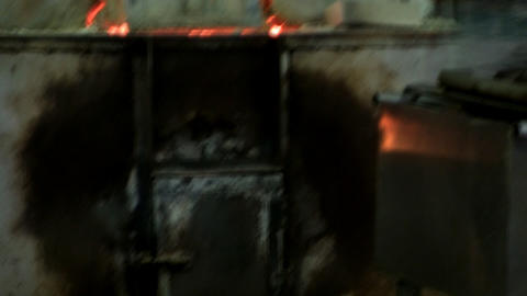 Gaffer picks up gather of molten glass from furnace, drains excess in bucket of  Footage