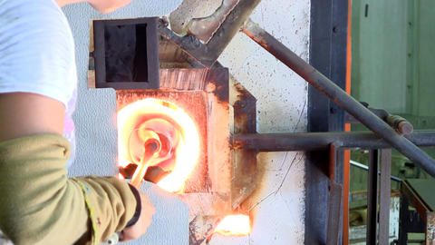 Multicolored vase spinning in furnace glory hole while glass artist stands behin Footage
