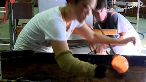 Japanese female glass artist shapes gather while assistant blows it up like ball Footage
