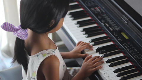 Asian girl learning to play piano Footage