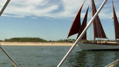 A Sailboat Passes Motor Boat While Leaving Harbor For Open Ocean On Cape Cod stock footage