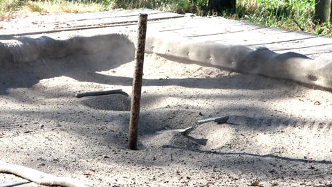 Horseshoes Landing Near Pole In Pit Of Sand Creates Dust In Sunlight stock footage