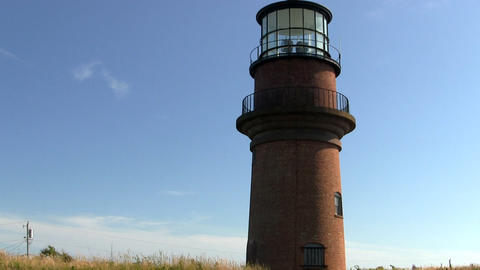 Lighthouse at Gay Head Aquinnah on Martha's Vineyard against bright blue sky on  Footage