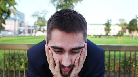 Sad Businessman Sitting In The Park, Depressed. Tracking shot Footage