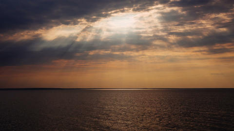 Timelapse of the beautiful sunset with sun rays trough clouds above sea Footage