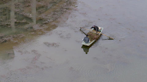 4K Two Men Transport Plants Removed from Lake in China Footage