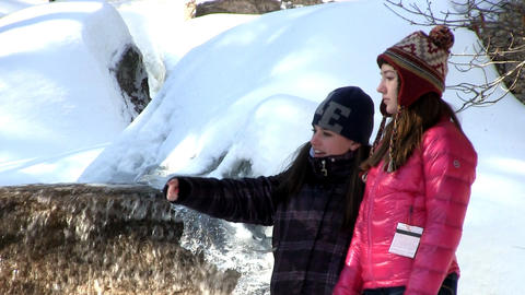 Teenage girls talking by water fall on winters day Footage