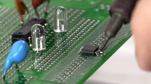 Soldering surface mount IC to circuit by hand Footage