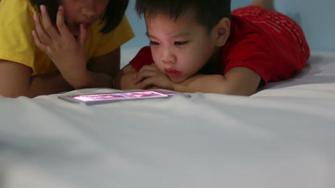 HD footage, close up boy and girl playing tablet pc at night Footage
