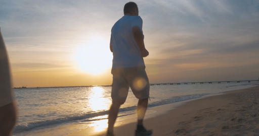 Evening jogging along the beach at sunset Footage