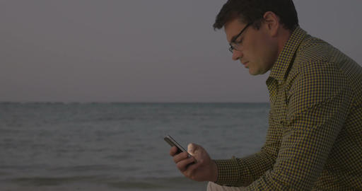 Young man using smart phone by sea in the evening Footage