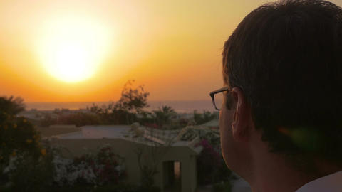Man putting on spectacles to enjoy the sunset Live Action