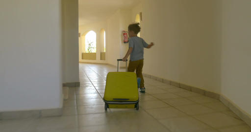 Child with rolling bag running along the hotel corridor Footage