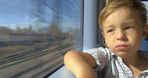 Little boy looking out train window on sunny day Footage