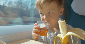 Little boy eats while travelling by train Footage