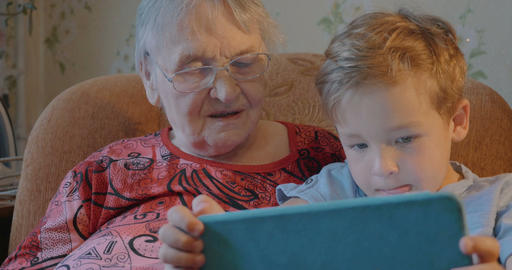 Boy Showing Something in Tablet to his Grandmother Footage