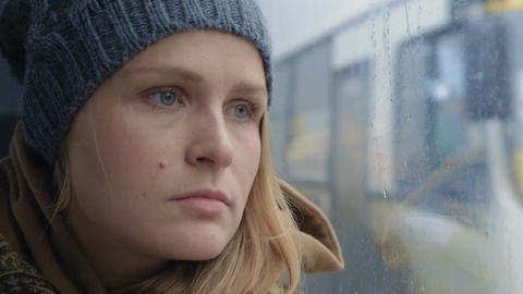 Frustrated and sad woman traveling by bus on rainy day Live Action