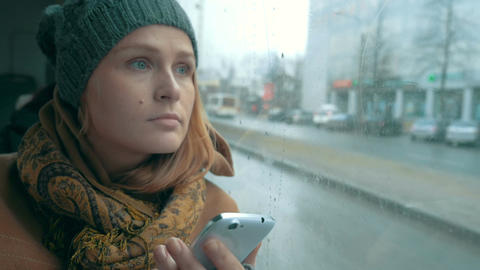 Woman using phone in bus on rainy day Footage