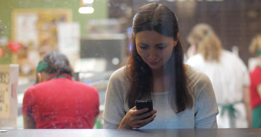 Young brunette girl using smartphone in the cafe Footage