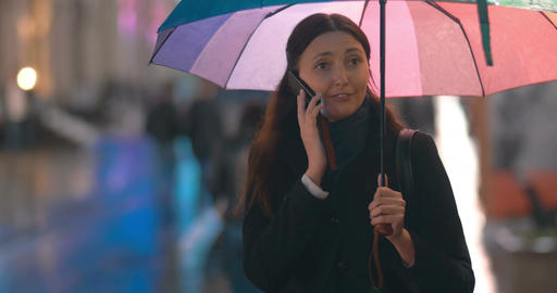 Young woman with umbrella talking on the phone Footage