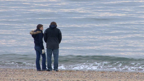 Young teenage couple whale watching from beach Footage