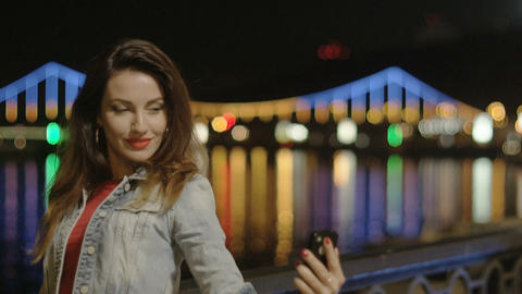Beautiful Funny Woman Making Selfie With A Phone At Night City At The River With stock footage