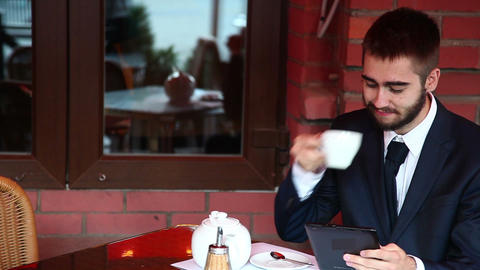 Attractive man in a cafe using a tablet Footage
