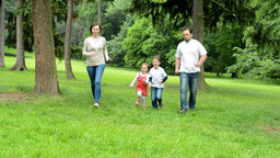 family (middle couple in love, cute girl and small boy) running in park from dis Footage