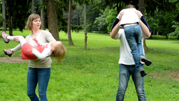 family (middle couple in love, cute girl and small boy) play together in park Footage