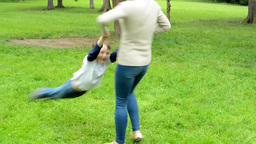 Mother rotate with son (little boy) around - park Footage
