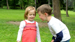 children (siblings - little boy and cute girl) talk in the park Footage