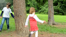 children (siblings - little boy and cute girl) playing in the park (running arou Footage
